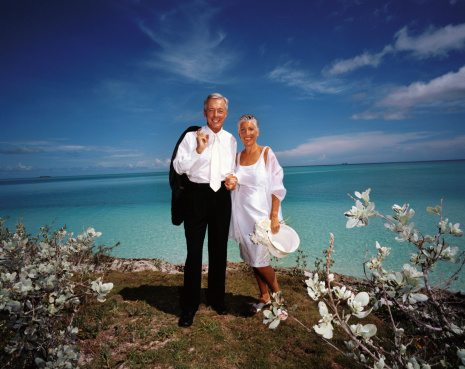 portrait of a newly wed mature couple standing by the sea
