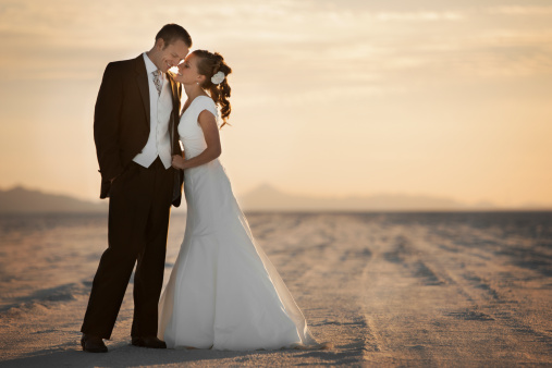 USA, Utah, Boneville Salt Flats, Bride and groom embracing in desert